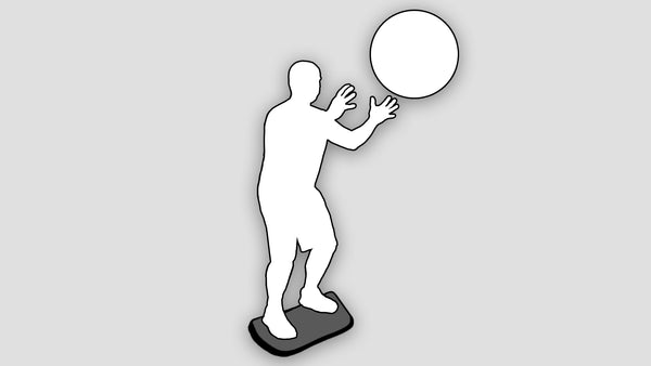 silhouette of man catching a ball on stability board