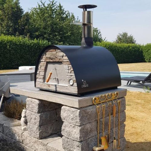 Image of Authentic Pizza Ovens Maximus Arena Countertop Wood Fired Pizza Oven in Black on Custom Built Stone and Concrete Base in Backyard