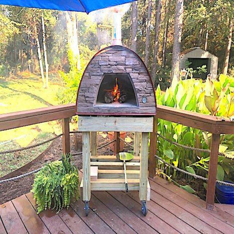 Authentic Pizza Ovens Maximus Prime Countertop Wood Fired Pizza Oven in Red on Custom Built Wood Cart on Back Porch with Fire Burning Inside Oven