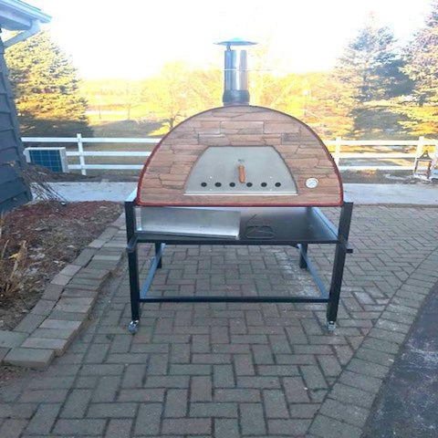 Image of Authentic Pizza Ovens Maximus Prime Countertop Wood Fired Pizza Oven in Red on Black Stand in Outdoor Patio