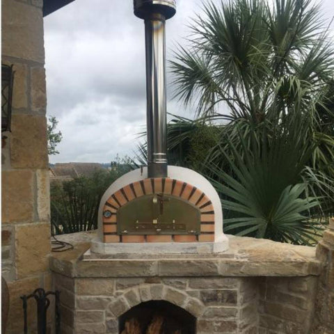 Image of Authentic Pizza Ovens Pizzaioli Countertop Wood Fired Pizza Oven with Chimney Pipe Extension and Chimney Cap Sitting on a Custom Built Stone Base in Back Patio