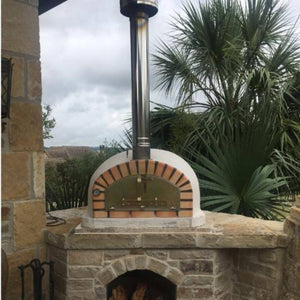 Authentic Pizza Ovens Pizzaioli Countertop Wood Fired Pizza Oven with Chimney Pipe Extension and Chimney Cap Sitting on a Custom Built Stone Base in Back Patio