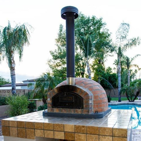 Authentic Pizza Ovens Premium Pizzaioli Rustic Finish Countertop Wood Fired Pizza Oven on Custom Built Tile Base in Backyard with Chimney Pipe Extension and Cap