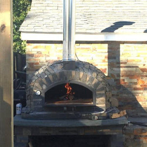 Authentic Pizza Ovens Premium Pizzaioli Stone Finish Countertop Wood Fired Pizza Oven on Back Patio with Fire Burning Inside Oven and Door Open