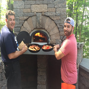 Chicago Brick Oven CBO 1000 Commercial Wood Fired Pizza Oven Kit Cooking Bratwursts and Vegetables with Father and Son