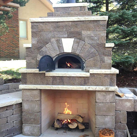 Chicago Brick Oven CBO 1000 Commercial Wood Fired Pizza Oven Kit Custom Stone Patio Installation with Fireplace Below Oven and Fire Burning in Both
