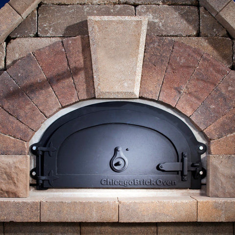 Chicago Brick Oven CBO 1000 Commercial Wood Fired Pizza Oven Kit with Door Closed in Custom Red Stone Installation
