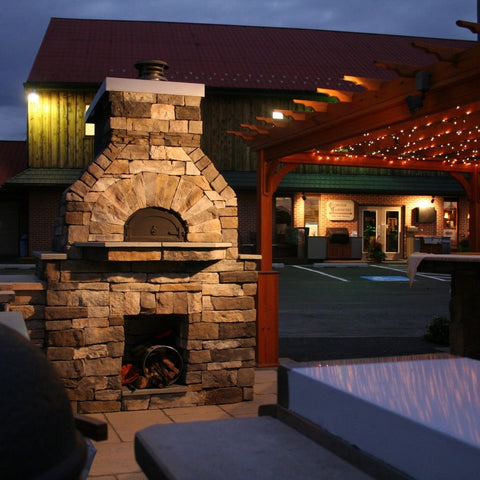 Chicago Brick Oven CBO 1000 Commercial Wood Fired Pizza Oven Kit Outdoor Restaurant Patio at Night with Pergola