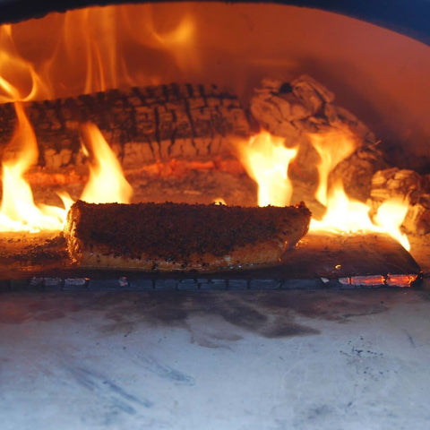 Image of Chicago Brick Oven CBO 500 Countertop Wood Fired Pizza Oven Cooking Fish with Fire Burning in the Background of the Oven
