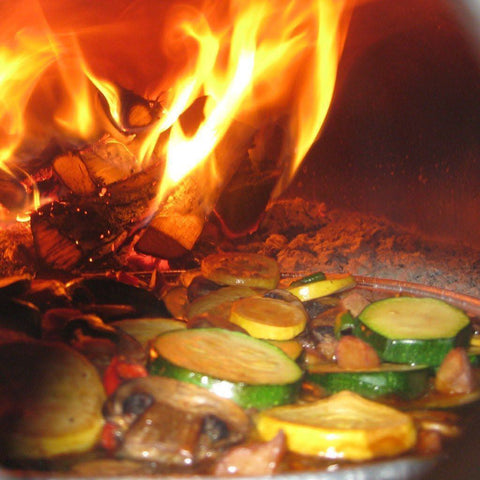 Image of Chicago Brick Oven CBO 500 Countertop Wood Fired Pizza Oven Cooking Vegetables with Fire Burning in the Background of the Oven