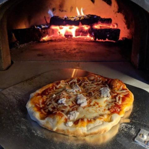 Chicago Brick Oven CBO 500 Wood Fired Pizza Oven Kit Cooking Pizza on a Pizza Peel with Wood Burning in the Oven