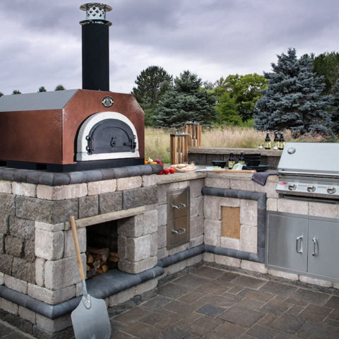 Chicago Brick Oven CBO 750 Countertop Wood Fired Pizza Oven in Copper Vein in Custom Built Outdoor Kitchen with Grill and Trees in the Background