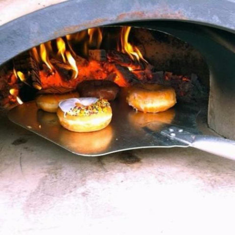 Chicago Brick Oven CBO 750 Commercial Wood Fired Pizza Oven Trailer Cooking Donuts with Fire Burning in the Background of the Oven