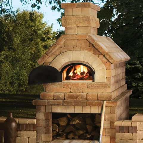 Chicago Brick Oven CBO 750 Wood Fired Pizza Oven DIY Kit Custom Backyard Stone Installation with Oven Door Open and Fire Burning in Summer