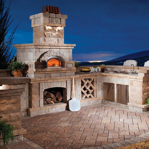 Chicago Brick Oven CBO 750 Wood Fired Pizza Oven DIY Kit in Custom Stone Outdoor Kitchen with Fireplace and Sink at Night
