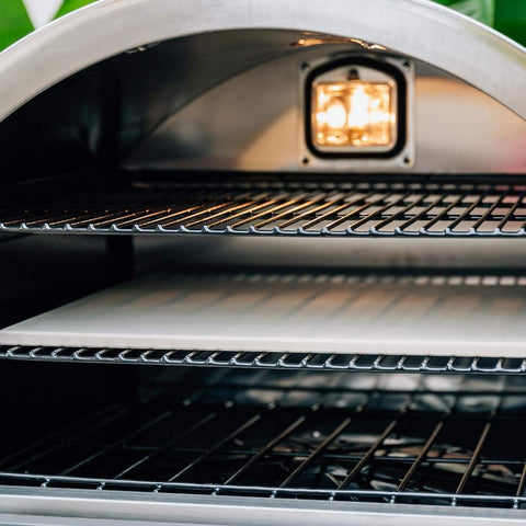 Summerset Built-In or Countertop Outdoor Gas Pizza Oven with Door Open Showing Three Levels of Cooking Grates with the Middle Cooking Grate Having a Pizza Stone on It and the Light On Within the Oven
