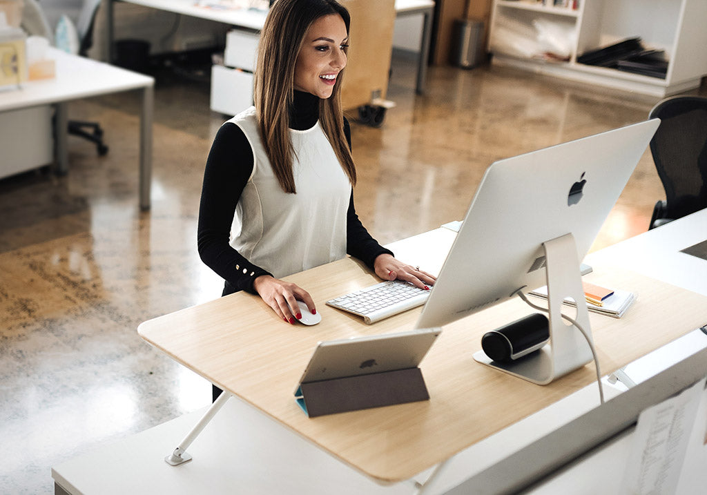 White | woman using computer at standing desk