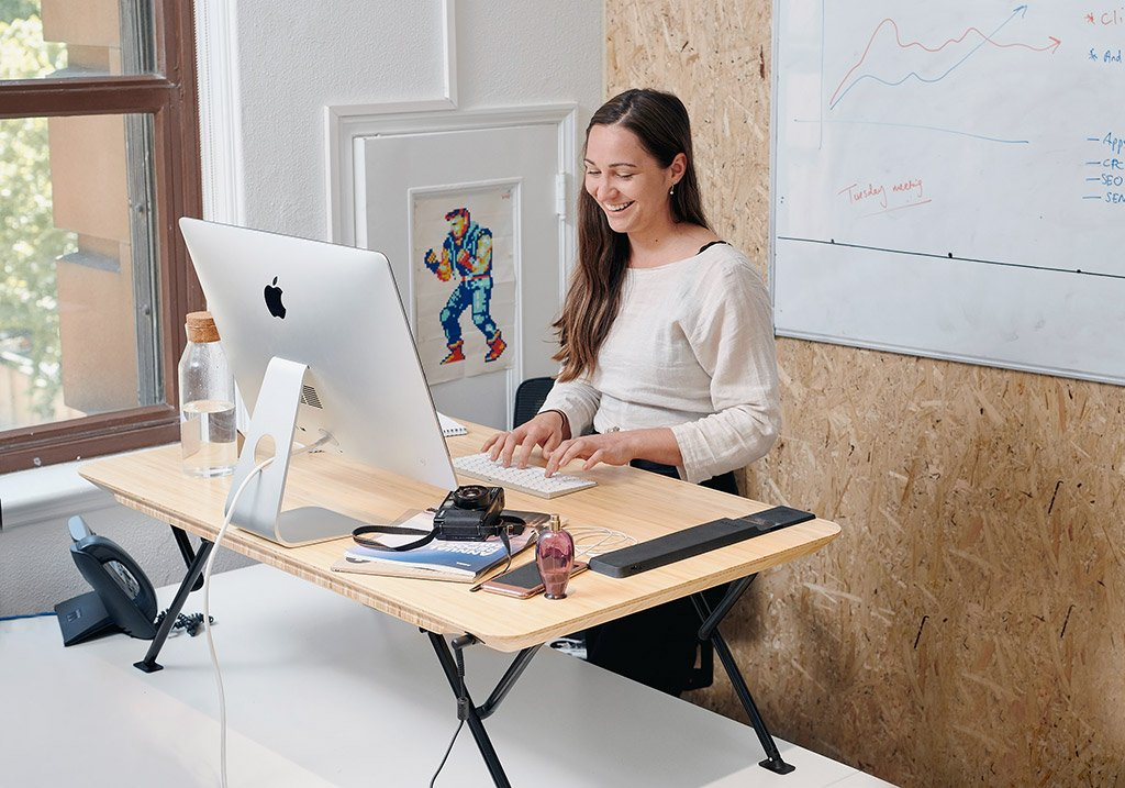 Black | woman typing at standing desk
