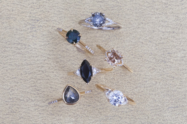 Waant rings showcasing champagne diamond, salt and pepper diamond, grey diamond, white diamond, black diamond, and Montana sapphire centers