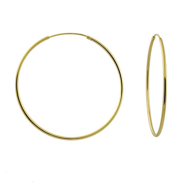 Gold big hoop earrings with a continuous fastening device.