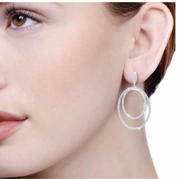 Lady wearing an oval within an oval earrings encrusted with CZ stones.