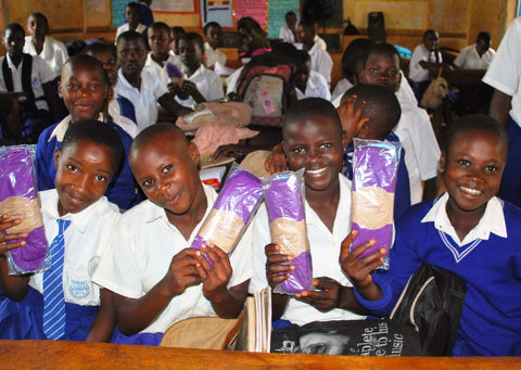 Girls' in Uganda holding their new, purple, reusable period products and menstrual pads donated by Just a Drop