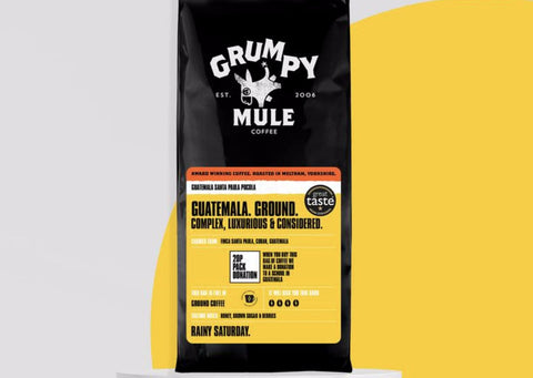 Grumpy Mule ethical coffee is in front of a yellow and grey background