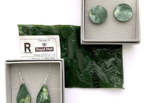 2 pairs of green and cream earrings in light grey boxes. In between the boxes there is a piece of green plastic from our mailer bags