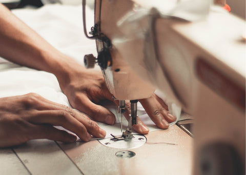 A pair of hands work at a sewing machine