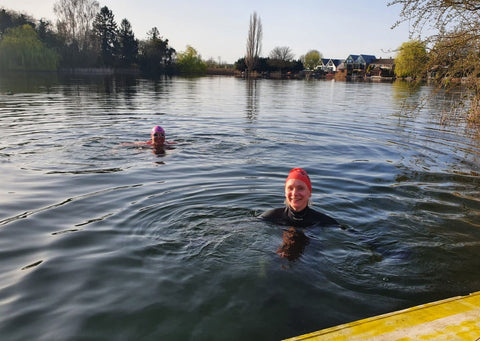 Sarah is in the bottom right corner, swimming outdoors in a deep blue lake. She's wearing a pink swimming cap and there is another swimmer to the back and right of her