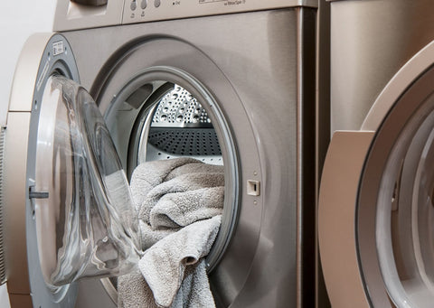 A grey-silver washing machine filled with laundry