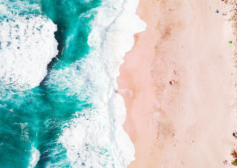 A turquoise blue sea washes up against a golden sand beach