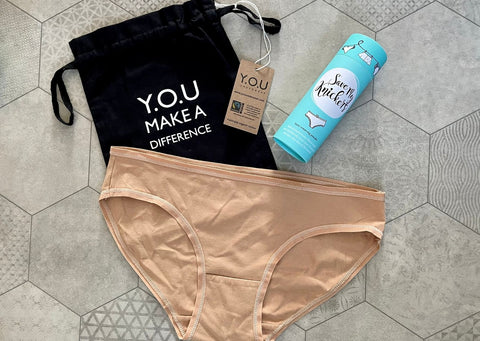 Y.O.U Underwear Organic Cotton Almond Bikini Bottoms are surrounded by the Save My Knickers blue tube and our packaging
