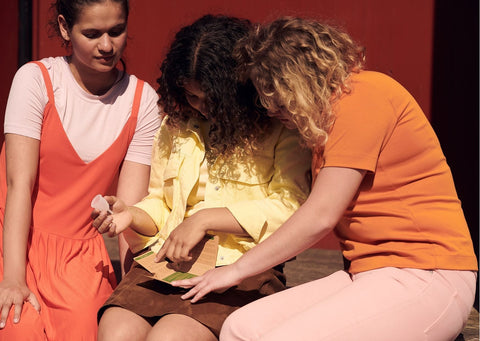 3 teens in bright clothes gather around an organicup cardboard box, reading the instructions