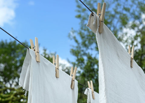White t-shirts hanging on a washing line with blue skies above