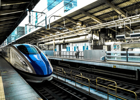 In a train station, a curved blue modern train waits at the platform