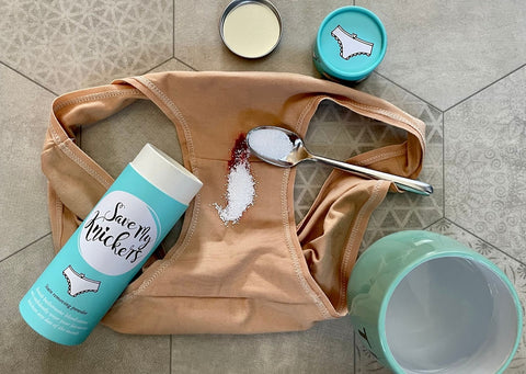 Organic Cotton Y.O.U underwear are surrounded by the Save My Knickers blue tube, a blue mug filled with water and a spoon is on the underwear