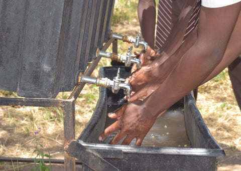 Children in Uganda washing their hands with soap provided by Just a Drop