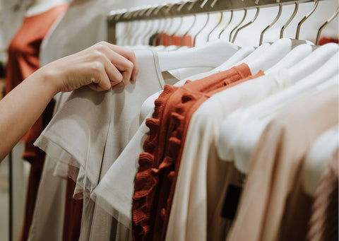 A hand picks out a shirt from a rail of beige, muted toned clothing