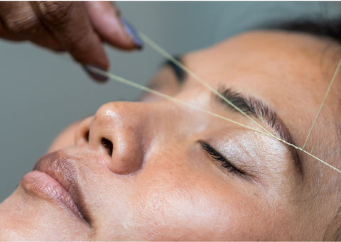 a woman's face, her dark brown eyebrows are being threaded
