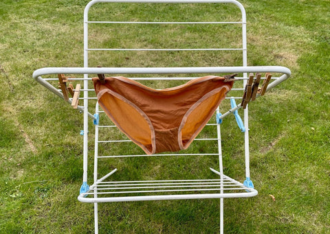 A pair of almond y.o.u underwear bikini bottoms hang in the garden on a clothes horse to dry