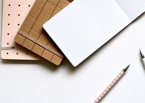 Pink, brown and white notebooks are placed over each other. In the bottom right there are 2 pens
