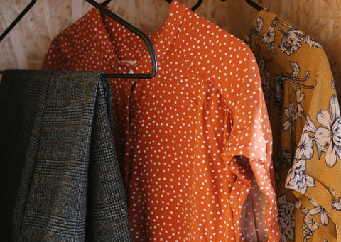3 Items of clothing on hangers. A pair of checked grey trousers, a coral coloured blouse with white spots and a yellow top with white flowers