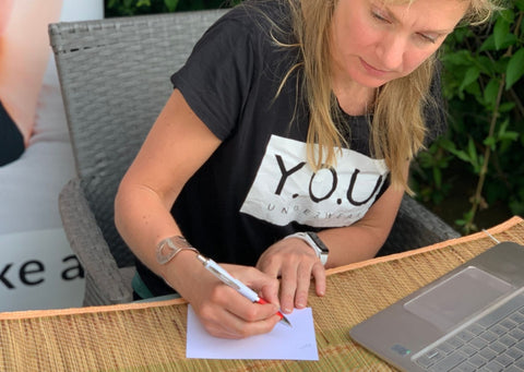 Our CEO, Sarah, wearing a 'Y.O.U' branded black T-Shirt, writing out thank you cards to be included in our packages in the sun!
