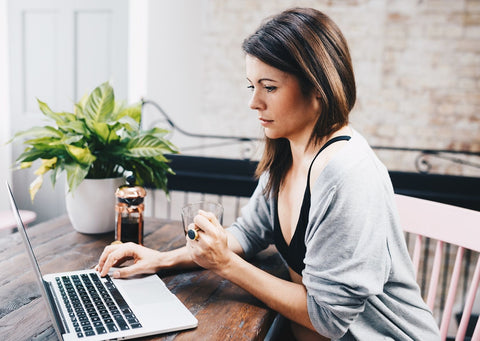 A dark haired woman sits at a wooden desk and uses her laptop. She's wearing a light blue shirt and Y.O.U Underwear black organic cotton underwear