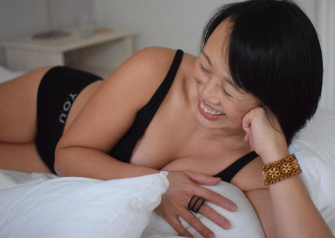 A woman lies on her side on a bed wearing Y.O.U Underwear organic cotton black branded boy shorts and bralette