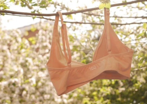 Almond Light Nude Bralette Hung on a Branch against green leaves and blossom