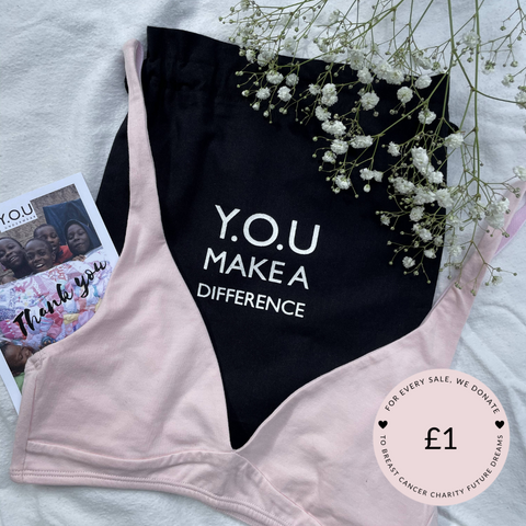 Our Light Pink Organic Cotton Bralette is on top of our 'Y.O.U Make A Difference' organic cotton black bag, there are white budded flowers in the top right corner