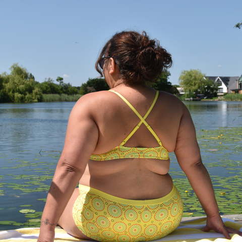 A brunette woman sits on the end of a pier looking at a lake in sustainable bralette and boy shorts in yellow mara from y.o.u underwear