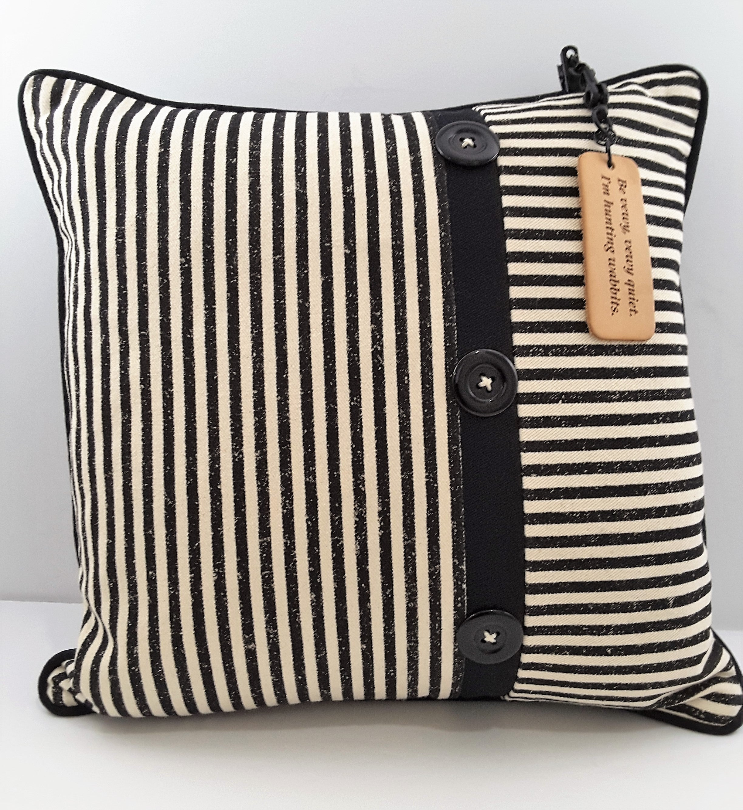 HANGING LEATHER PILLOW TAG ON BLACK AND NATURAL STRIPE PILLOW